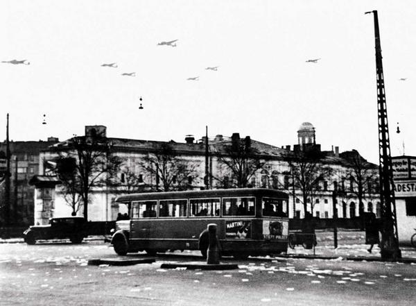 """Tyske bombemaskiner over København 9. april 1940. På gaden ligger flyveblade med titlen """"Opror"""", som den tyske værnemagt har kastet ned for at informere om, at Danmark nu er besat. Besættelsen varede frem til 5. maj 1945 og kom til at påvirke den litteratur, der blev skrevet i perioden."""